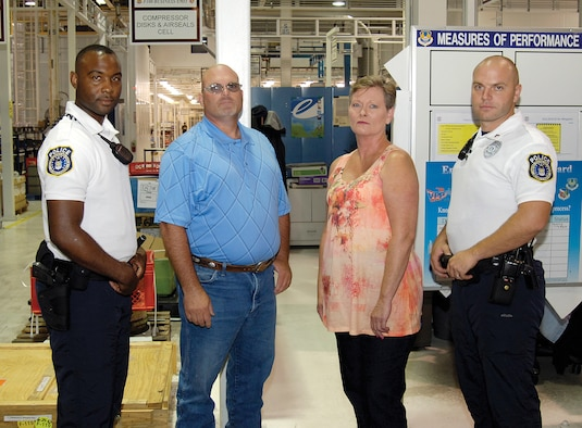 Tech. Sgt. Keith Hagins, 72nd Security Forces Squadron; Rodney Walker and Cheryl Sweeney, both of the 544th Propulsion Maintenance Squadron; and officer Aaron Whitehead, 72nd SFS, from left, acted instinctively, demonstrating the highest example of being Wingmen when they saved the life of a 544th PMXS co-worker found June 18 crumpled on the floor of his Bldg. 3001 work area, shown behind them in the F100 Compressor Cell. (Air Force photo by Margo Wright)
