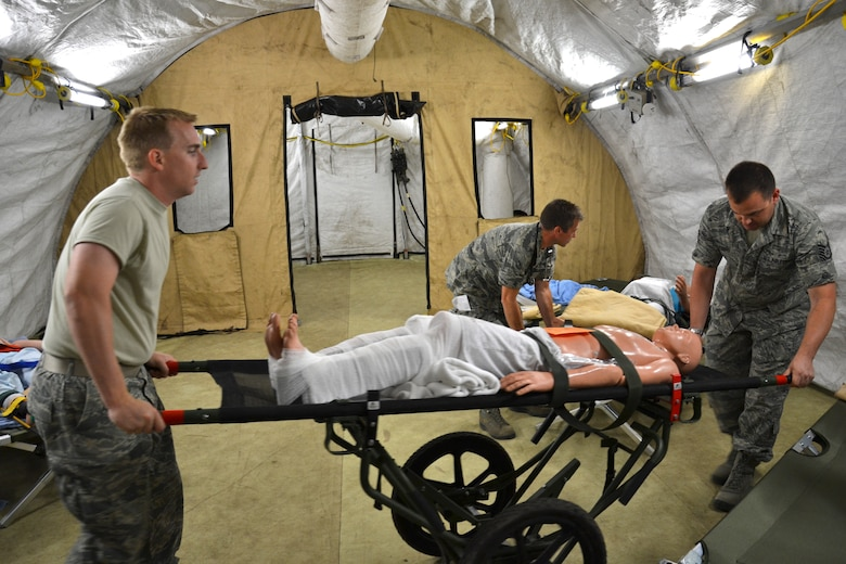"""Tech. Sgt. Danny Watton and Tech. Sgt. Travis Davis, medical technicians from the Arizona Air National Guard's 162nd Medical Group, transport a mock patient with a bi-lateral femur fracture from the emergency room to the ward in an Expeditionary Medical Support field hospital. The medical technicians were participating in """"real world"""" exercises at the Alpena Combat Readiness Training Center in Michigan. (U.S. Air Force photo/Master Sgt. Cally Handa)"""