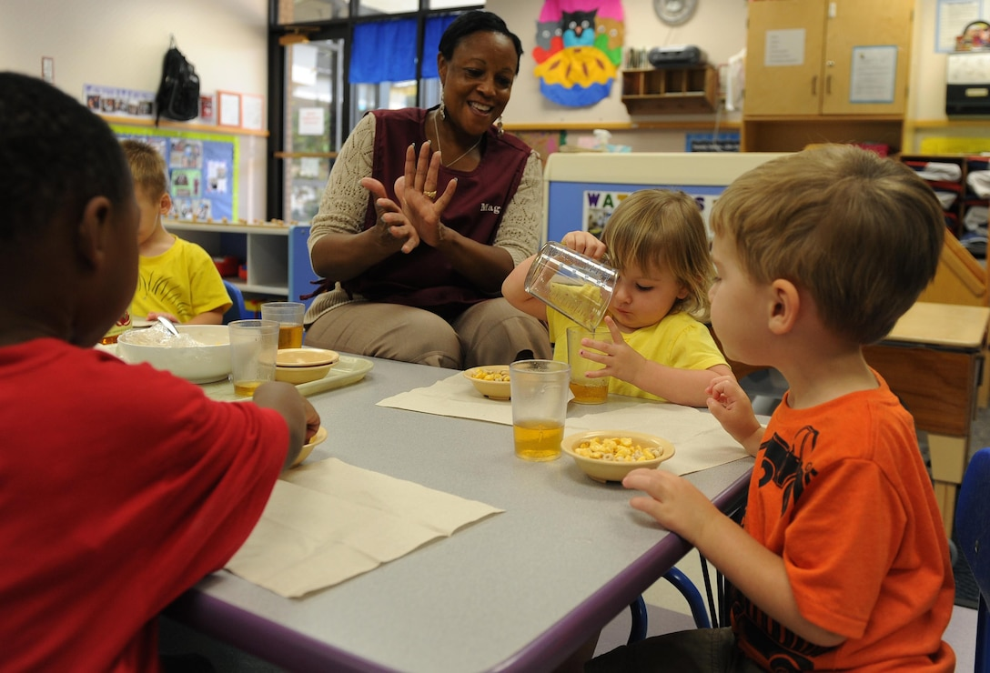 Maggie Miller, room lead teacher, helps toddlers pour juice during snack time July 10, at Little Rock Air Force Base, Ark. Teachers in the toddler room help teach the children to say 'thank you', 'please', and learn the basic table manners. (U.S. Air Force photo by Airman 1st Class Ellora Remington)