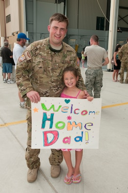 Tech. Sgt. Jeremy Fallecker, Flight Engineer with the 130th Airlift Wing, West Virginia Air National Guard, poses with his daughter after returning to Charleston, West Virginia from a 120-day deployment to Afghanistan and Kuwait in support of Operation Enduring Freedom.  U.S. Air Force Photo by TSgt Bryan G. Stevens [Photo Released]
