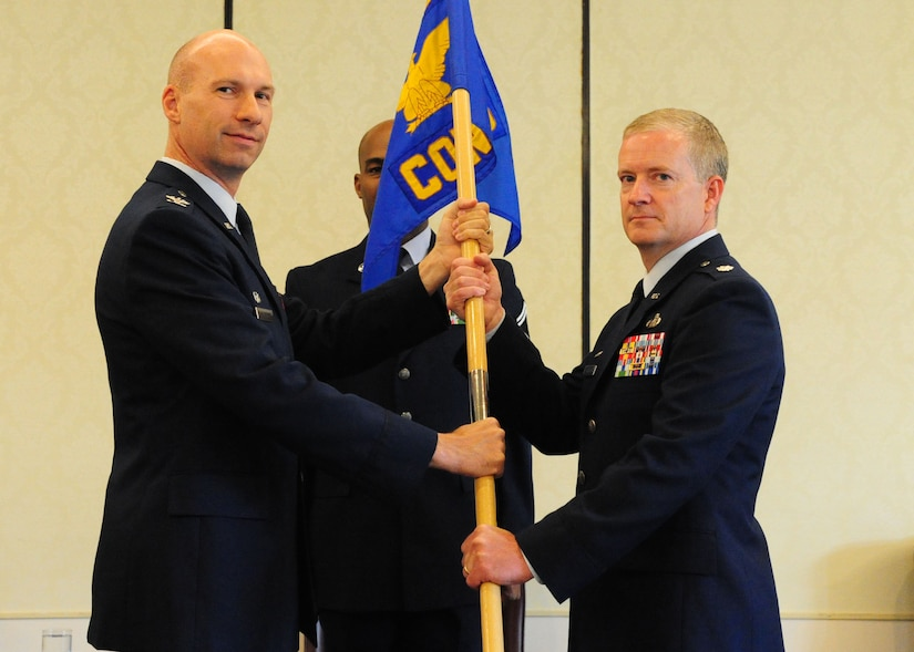 Colonel Justin Davey, 628th Mission Support Group commander, hands the guidon to Lt. Col. Dale Skinner, 628th Contracting Squadron incoming commander, during the 628th CONS Change of Command Ceremony at Joint Base Charleston - Air Base, S.C, July 16, 2012. The passing of the guidon symbolizes the changing of a command. (U.S. Air Force photo/ Airman 1st Class Chacarra Walker)