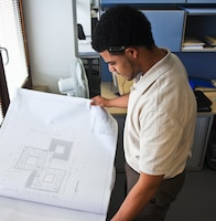 WIESBADEN, Germany -- Lucas Suarez, Advancing Minorities' Interest in Engineering (AMIE) intern, reviews some blueprints for a construction project in Israel while working with the Project Management department at the Amelia Earhart here, July 10, 2012.
