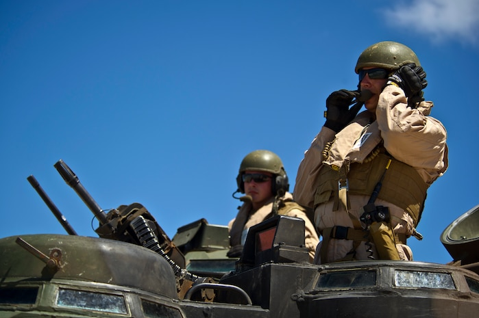 Sgt. Nolan Lynch, Combat Assault Company, 3rd Marine Regiment, communicates through a headset to the other Amphibious Assault Vehicle crew members prior to entering the water off Pyramid Rock beach July 12, to meet up with the USS Essex (LHD-2) off shore during Rim of the Pacific Exercise (RIMPAC) 2012. Approximately 2,200 troops from nine countries are part of the Combined Force Land Component Command, and will be conducting amphibious and land-based operations throughout the exercise in order to enhance mutual capabilities and joint interoperability.