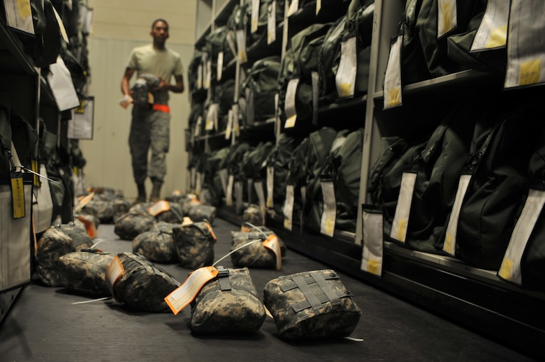 U.S. Air Force Airman 1st Class Ryan Williams, 27th Special Operations Logistics Readiness Squadron material management flight, collects expired individual first aid kits that were removed from several mobility bags at Cannon Air Force Base, N.M., July 17, 2012. The material management flight stocks and issues 26,000 line items of supplies and equipment, including mobility bags and weapons. (U.S. Air Force photo/Airman 1st Class Eboni Reece)