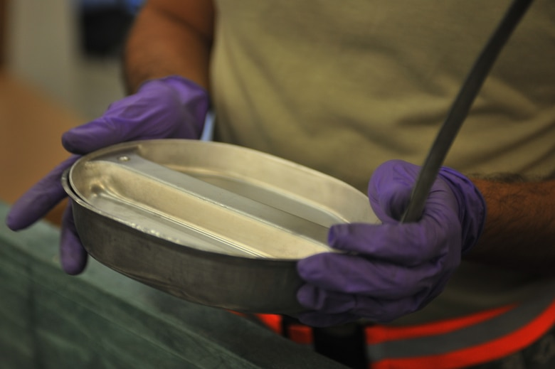 U.S. Air Force Staff Sgt. Santos Delacruz, 27th Special Operations Logistics Readiness Squadron material management flight, holds a mess kit at Cannon Air Force Base, N.M., July 18, 2012. The need for mess kits to serve military rations is no longer necessary, as they were replaced by Meals, Ready to Eat. (U.S. Air Force photo/Airman 1st Class Eboni Reece)