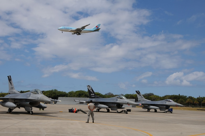 A crew chief from the 144th Fighter Wing stands alert until the F-16 Fighter jet has clearance to take off during RIMPAC 2012. The 2012 Rim of the Pacific exercise is the twenty-third maneuver in a history of bi-annual drills that dates back four decades. The purpose of the exercise is to bring together nations to observe, train and exchange information that fosters a cooperative training environment.  (Air National Guard photograph by MSgt. David J. Loeffler)