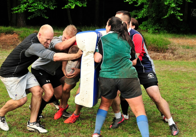 Members of the Ramstein Rogues collide during a ruck drill during a preseason practice at the 435th Construction Training Squadron rugby pitch at Ramstein Air Base, Germany, July 12, 2012. The Rogues have two men's teams and one women's team consisting of Host Nation players, British Royal Air Force and U.S. military Soldiers, Airmen from the Kaiserslautern area and dependents. (U.S. Air Force photo/Airman 1st Class Trevor Rhynes)