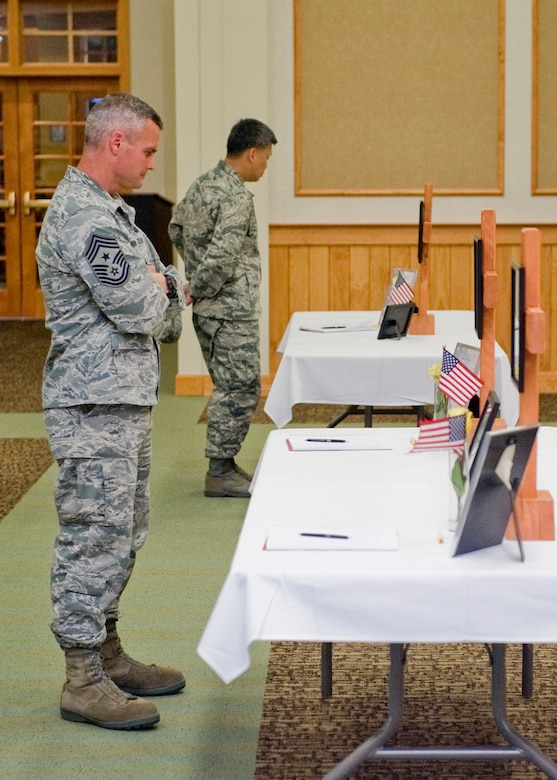 Anderson, left, and Col. H.B. Brual, 341st Missile Wing commander, browse memorials for several security forces Airmen during a ceremony in honor of Memorial Day.  His assignment here at Malmstrom marked his second time serving as a command chief for a wing.  (U.S. Air Force photo/Beau Wade)