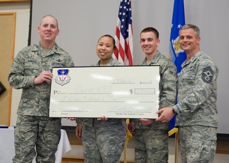 Chief Master Sgt. Charles Anderson, 341st Missile Wing command chief, far right, and Col. Edward Rimback, 341st Operations Group commander, far left, present two Dorm 635 residents with a $1,500 check for the winning the Dorm of the Quarter award.  Anderson has served in several different positions during his Air Force career, and has traveled a good portion of the world.  (U.S. Air Force photo/Beau Wade)