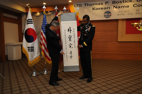 "SEOUL, Republic of Korea – Suh Jin-sup, chairman of the Republic of Korea-U.S. Alliance Friendship Association, points to Korean characters on a scroll as he reads them to Lt. Gen. Thomas Bostick, the Chief of U.S. Army Engineers and Commanding General of the U.S. Army Corps of Engineers, during a ""Korean naming ceremony"" July 16.  Bostick was given the honorific Korean name Park Bo-taek by the association during his visit to the Republic of Korea, where he met with U.S. and Korean military officials and toured the multi-billion dollar construction project at U.S. Army Garrison Humphreys, about 40 miles south of Seoul.   Bostick's visit to the Corps of Engineers Far East District in Korea was his first since assuming command May 22.  The Corps of Engineers has about 37,600 military and civilian personnel providing project management and construction support in more than 100 countries.  U.S. Army photo by Patrick Bray."