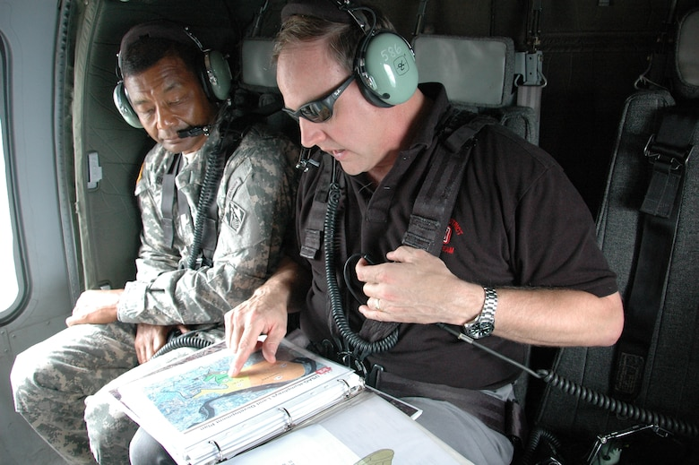 SOUTH OF SEOUL, Republic of Korea Lt. Gen. Thomas Bostick listens to Far East District area engineer Greg Reiff during a flight to U.S. Army Garrison Humphreys, as he briefs him on construction progress at the facility, about 40 miles south of Seoul.   Bostick, the Chief of U.S. Army Engineers and Commanding General of the U.S. Army Corps of Engineers, was in Korea July 16-17 meeting with U.S. and Korean military officials and touring the multi-billion dollar construction project at Humphreys. Bostick's visit to the Corps of Engineers Far East District in Korea was his first since assuming command May 22.  The Corps of Engineers has about 37,600 military and civilian personnel providing project management and construction support in more than 100 countries. U.S. Army photo by Jason Chudy.