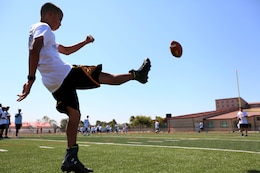 Joseph Ramirez, 13, kicks a football during a punting drill. Young aspiring athletes, ages 6-17, received coaching from former professional athletes during the 2nd Annual Eric Dickerson Foundation Youth Football and Cheer Camp at Camp Pendleton's Paige Fieldhouse, July 19 and 20.