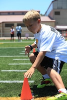 A young athlete touches a cone before dashing to another during a sprint drill. On July 19 and 20, military family youth paprticipants took part in mini-training camps, providing football and cheerleading mentorship from former professional athletes, at Camp pendleton's Paige Fieldhouse.