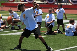 A young athlete prepares to launch a pass during a passing drill. On July 19 and 20, military family youth participants took part in mini-training camps, providing football and cheerleading mentorship from former professional athletes, at Camp Pendleton's Paige Fieldhouse.