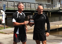 Lt Col. David Bardorf (left), commanding officer of Headquarters and Support Battalion, presents 1st Sgt. Dustin Kazmar, the former first sergeant of Company B, with the Commander's Cup trophy for winning the paddleboarding relay-race July 20 at Gottschalk Marina aboard Marine Corps Base Camp Lejeune. This competition was the last challenge Kazmar will be participating in.