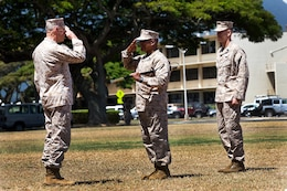 Sgt. Maj. James R. Futrell (center), U.S. Marine Corps Forces, Pacific sergeant major, salutes Lt. Gen. Duane D. Thiessen (left), commander of MarForPac, before passing the noncommissioned officer sword during the relief, appointment and retirement ceremony at Dewey Square here July 19. The transfer of the NCO sword, a symbol of an NCO's ability and prestige as an enlisted leader, signifies the transfer of the sacred trust of the office from one sergeant major to another.  Futrell was replaced by Sgt. Maj. William T. Stables (right).