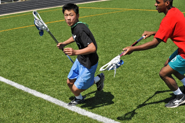 BUCKLEY AIR FORCE BASE, Colo. -- Josh Maples, left, makes his way to the net as Alex Vasquez defends him during a game of lacrosse July 17, at the Buckley outdoor track and field. During the week children were able to participate in unique sports including fencing, hand ball and badminton in hopes to broaden their sports horizon. (U.S. Air Force photo by Senior Airman Christopher Gross)