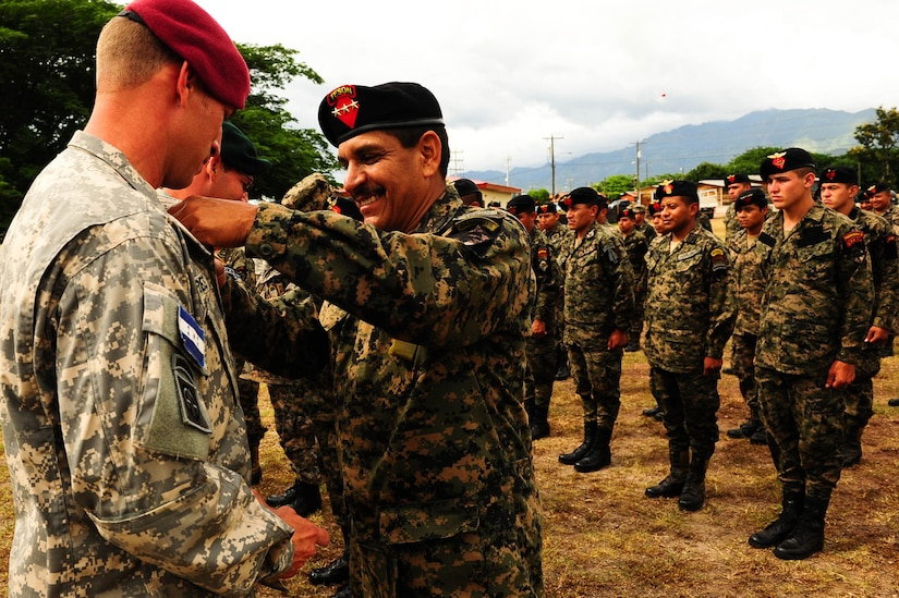 SOTO CANO AB, Honduras – A Honduran jumpmaster presents a U.S. Army jumpmaster Honduran jump wings during a wing exchange ceremony following a combined airborne exercise at Joint Task Force-Bravo.  (U.S. Air Force photo by 1st Lt. Christopher Diaz)