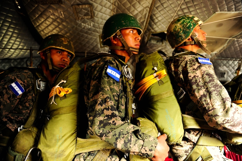 SOTO CANO AB, Honduras – Honduran army paratroopers stand up and hold the static line in a CH-47 Chinook helicopter, listening closely to their jumpmaster's commands during a combined airborne exercise at Joint Task Force-Bravo. (U.S. Air Force photo by 1st Lt. Christopher Diaz)
