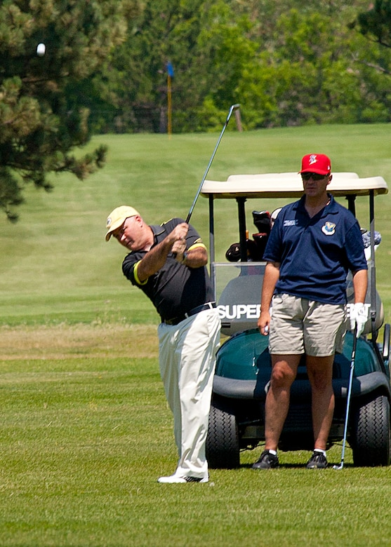 "Maj. Gen. Michael J. Carey, 20th Air Force commander, drives the ball off the fairway as Chief Master Sgt. David Nordel, 20th AF command chief, looks on during the Military Affairs Committee golf tournament July 13, at the Warren Golf Course. The event drew 100 players from the Warren community, Cheyenne and the surrounding area. ""We had 20 local businesses sponsor the event this afternoon,"" said Jim Wood, incoming MAC chairman. ""We were able to raise more than $5,000 to help support our troops, and provide education to the community about what our servicemembers do. I'm happy everyone enjoyed themselves while making this event a success."" (U.S. Air Force photo by Matt Bilden)"
