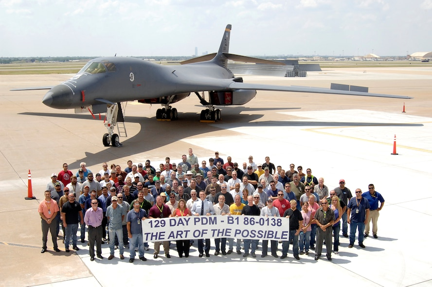 A banner says it all for the Oklahoma City Air Logistics Complex mechanics who produced a B-1 Bomber early and proudly delivered it to the customer this month.  Maintainers on the bomber even beat their own tight goals by finishing in 129 days. (Air Force photo by Margo Wright)