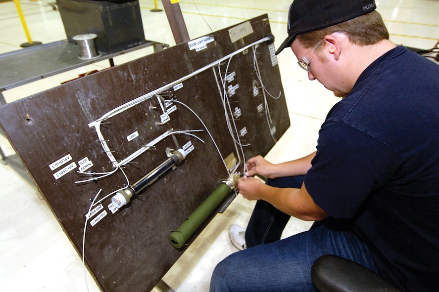 Chance Stevens came to the Boom Shop three months ago and with seasoned personnel working with him, is enjoying learning work in the shop.  Mr. Stevens follows a wiring cables outline to reconnect electrical for lights and hydraulics that are installed in the tail cone.  The system will then be tested as used on the boom before installed in a waiting tail cone.  In flight, the lights help guide the refueler and the receiver in making a safe connection before refueling begins.(Air Force photo by Margo Wright)