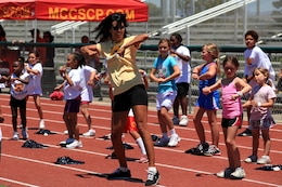 Youth cheerleaders follow along with their coach during a cheer routine. Young, aspiring athletes, ages 6-17, received coaching from former professional athletes during the 2nd Annual Eric Dickerson Foundation Youth Football and Cheer Camp at Camp Pendleton's Paige Fieldhouse, July 19 and 20.