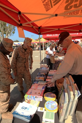 Marines look at information provided by Marine and Family Programs displayed at the 13th annual San Onofre Community Center Community Day Celebration, July 21. Booths set-up around the parking lot offered crafts, giveaways and resources about that organization located on base or in the surrounding community.