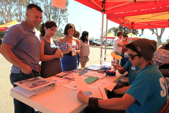 A family attending the 13th annual Community Day Celebration looks at information about youth programs at the San Onofre Community Center, July 21. The Community Day Celebration is held to give service members and their families information about the surrounding community.