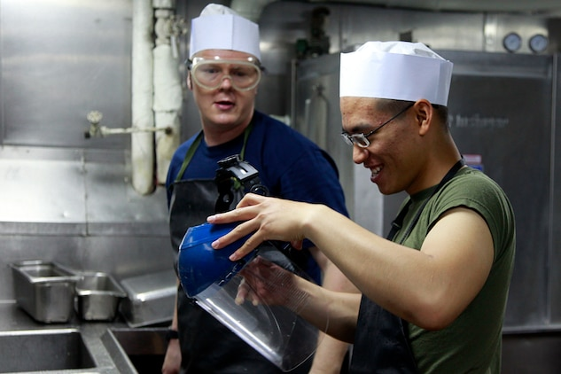 Lance Cpl. Paul D. Hoang (right,) electro-optical ordnance repairer, Headquarters and Service Company, Battalion Landing Team 3/5, 15th Marine Expeditionary Unit, and Airman Jiri Gajdacek, USS Peleliu, clean dishes in the ship's galley, July 22. Hoang and Gajdacek are both temporarily serving as mess men, a duty assigned to Marines and sailors to assist the food service specialists who prepare the meals for the Marines and sailors of the 15th Marine Expeditionary Unit and Peleliu Amphibious Ready Group. Hoang, 20, is from Houston, and Gajdacek, 30, is from Havirov, Czech Republic.