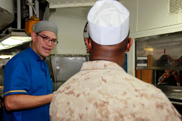 Petty Officer 3rd Class Julio J. Lopez (left,) culinary specialist, USS Peleliu, discusses food service preparation techniques with Lance Cpl. James T. Payne, food service specialist, Headquarters and Service Company, Battalion Landing Team 3/5, 15th Marine Expeditionary Unit, in the ship's galley, July 22. Lopez, 24, is from Denver and Payne, 22, is from Memphis, Tenn. The two prepare lunch and dinner for the Marines and sailors of the 15th Marine Expeditionary Unit and Peleliu Amphibious Ready Group.