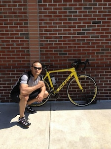 Tech Sgt. David Perez, a U.S. Cyber Command directorate of logistics at Fort Meade, Md., poses beside the Scott Foil bike he rode in the Black Water duathlon in Cambridge, Md., on June 3, 2012.  Perez performed so well at the event, he was invited to represent the U.S. National Team at the 2012 Long Course Duathlon World Championships which will take place September 2, 2012, in Zofingen, Switzerland. (Courtesy photo)