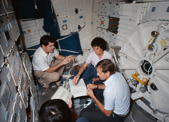 STS-34 crewmembers review inflight maintenance procedures on the mid deck of the Crew Compartment Trainer (CCT) in July 1989. A trainer, holding the cable, discusses procedures with Mission Specialist Ellen S. Baker (center) and Pilot Michael J. McCulley. An open stowage locker appears in front of the group. Visible on the mockup's mid deck are forward and aft stowage lockers, the airlock hatch and the starboard wall-mounted sleep restraints. (NASA photo)