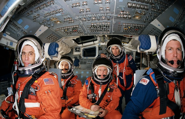 """STS-29 crewmembers, wearing launch and entry suits, participate in exercises in the Crew Compartment Trainer (CCT) in February 1989. Four crewmembers are pictured in the stations they will man for entry phase of the mission. They are joined by the fifth crewmember, """"borrowed"""" from the mid deck. At forward controls are Pilot John E. Blaha (left) and Commander Michael L. Coats. Behind them are Mission Specialists James P. Bagian (left) and James F. Buchli. Mission Specialist Robert C. Springer stands at aft station. Springer will occupy Discovery's mid deck for entry phase of the flight while Bagian will occupy that post for launch. (NASA photo by Bill Bowers)"""