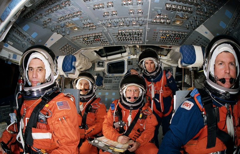 "STS-29 crewmembers, wearing launch and entry suits, participate in exercises in the Crew Compartment Trainer (CCT) in February 1989. Four crewmembers are pictured in the stations they will man for entry phase of the mission. They are joined by the fifth crewmember, ""borrowed"" from the mid deck. At forward controls are Pilot John E. Blaha (left) and Commander Michael L. Coats. Behind them are Mission Specialists James P. Bagian (left) and James F. Buchli. Mission Specialist Robert C. Springer stands at aft station. Springer will occupy Discovery's mid deck for entry phase of the flight while Bagian will occupy that post for launch. (NASA photo by Bill Bowers)"