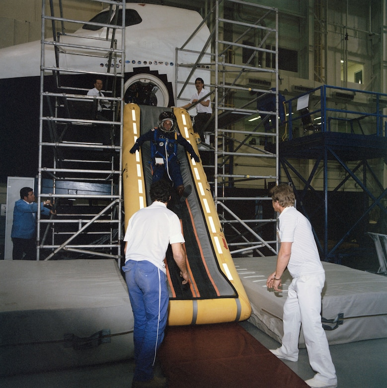 STS-26 Mission Specialist George D. Nelson trains in the Crew Compartment Trainer (CCT) located in Johnson Space Center's Shuttle Mockup and Integration Laboratory in March 1988. Nelson, wearing a partial pressure suit and helmet, exits the CCT via a slide inflated at the side hatch. Technicians at the bottom of the slide prepare to help Nelson to his feet as a second set of technicians observe the activity from scaffolding on either side of the open hatch. (NASA photo)