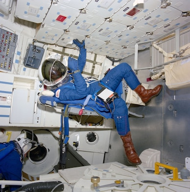 Astronaut George D. Nelson, STS-26 mission specialist, is followed into the mid deck by an unidentified crewmember in the crew compartment trainer (CCT) in the Shuttle Mockup and Integration Laboratory during a March 10, 1988, crew station review. The crew donned new partial pressure suits to evaluate crew equipment and procedures related to emergency egress methods and proposed crew escape options. (NASA photo)