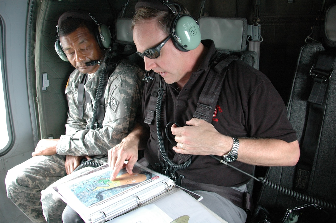 REPUBLIC OF KOREA — Lt. Gen. Thomas Bostick, U.S. Army Corps of Engineers commanding general, listens to Far East District area engineer Greg Reiff during a flight to U.S. Army Garrison Humphreys, as he briefs him on construction progress at the facility, about 40 miles south of Seoul. Bostick was in Korea July 16-17, 2012 meeting with U.S. and Korean military officials and touring the multi-billion dollar construction project at Humphreys. The Corps of Engineers has about 37,600 military and civilian personnel providing project management and construction support in more than 100 countries.