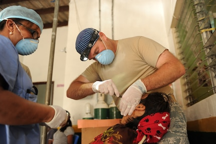 Air Force Maj. Brent Waldman, dentist, JTF-Bravo Medical Element, extracts a tooth from a Guna woman on the Island of Carti, during a Medical Readiness Training Exercise off the northeastern coast of Panama, July 17. Waldman dentists from the JTF-Bravo and the Panama Ministry of Health extracted thousands of teeth during the four day exercise. The Guna people so appreciated his work that a Guna woman named her son after him. (Official photo by Tech. Sgt. Brannen Parrish)