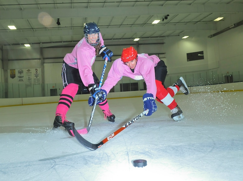 SAN ANTONIO -- 1st Lt. Andrew Caulk, right, of the Air Force Intelligence, Surveillance and Reconnaissance Agency and 1st Lt. Jennifer Caulk from the 453 Electronic Warfare Squadron at Lackland Air Force Base, Texas, battle for the puck July 20 at the Ice and Golf Center at Northwoods here, following their game in the Adult Recreational Hockey League. Hockey is one of many sports the duo plays for fitness, fun and quality time together. (U. S. Air Force photo  by William Belcher)