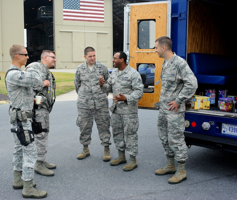 """Staff Sgt. Javon Merritte (second from right), chaplain's assistant with the 436th Airlift Wing, builds rapport with Airmen on the flightline at Dover Air Force Base, Del., July 20, 2012. Chaplain's assistants form religious support teams with chaplains to get face time with troops, sometimes utilizing the """"Holy Roller"""", a supply vehicle, to distribute food and drinks to those who work outside in the elements. (U.S. Air Force photo by Airman 1st Class Kathryn Stilwell)"""
