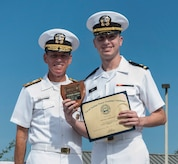 Ensign Paul Gale receives the Behrens award for Officer Class 1202 from Rear Adm. Richard Breckenridge, Submarine Group Two commander, during the Naval Nuclear Power Training Command graduation ceremony July 20, 2012, at Joint Base Charleston - Weapons Station, S.C. The Behrens award is given to the officer with the highest grade point average. (U.S. Air Force photo/Airman 1st Class Ashlee Galloway)