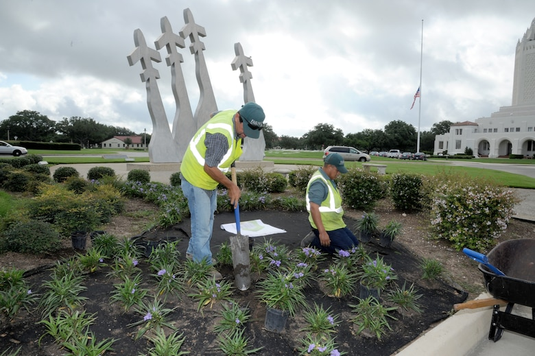 Hector Montoya (left), and Hector Perez, Fairways Landscaping service professionals, plant flowers around the Missing Man Monument on Joint Base San Antonio-Randolph, Texas, July 24. (U.S. Air Force photo by Rich McFadden)