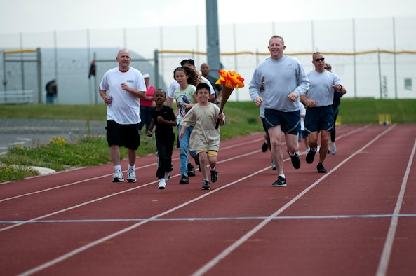 SPANGDAHLEM AIR BASE, Germany -- Ethan Guinn runs with an Olympic torch during the Olympic Day celebration near the Skelton Memorial Fitness Center here July 21.  Col. Joseph McFall, 52nd Fighter Wing vice commander,  Col. Scott Calisti, 52nd Mission Support Group commander, Maj. Catherine Logan, 52nd Force Support Squadron commander, and Chief Master Sgt. Matthew Grengs, 52nd Fighter Wing command chief, joined Ethan during the run. (U.S. Air Force photo by Airman 1st Class Gustavo Castillo/Released)