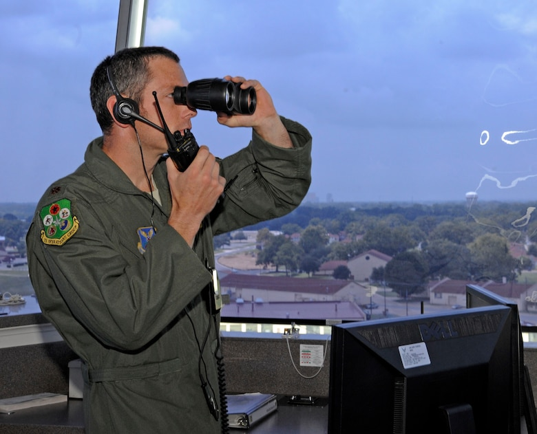 Maj. Matthew Pommer, 96th Bomb Squadron supervisor of flying, scans along the horizon from the air traffic control tower at Barksdale Air Force Base, La., July 23. The role of a SOF is to inform the operations group commander of scheduled flights and weather conditions, as well as ensure aircrew follow procedures safely. (U.S. Air Force photo/Airman 1st Class Andrew Moua)(RELEASED)