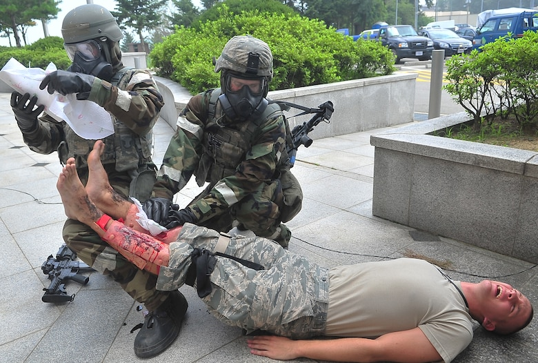 A pair of security sentries use expedient measures to protect the simulated wounds of a role player following a mass casualty event July 25, 2012, during exercise Beverly Midnight 12-03 at Osan Air Base, Republic of Korea.  Role players are pulled from 51st Fighter Wing units for the duration of the exercise.  Some of them are so new to the base, they have yet to join their units.  (Air Force photo/Tech. Sgt. Raymond Mills)