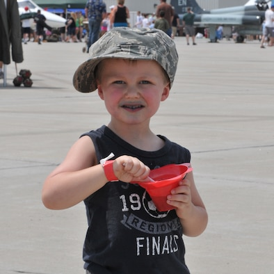 SIOUX FALLS, S.D. - Parker Stewart, son of Master Sgt. Christopher Stewart, 114th Public Affairs photographer, cools off with a  snow cone during Sioux Falls Airshow 2012. The 114th Fighter Wing hosted the airshow in conjuction with the city and also used the day as Family Day for it's units members and families.(National Guard photo by Master Sgt. Christopher Stewart)(Released)