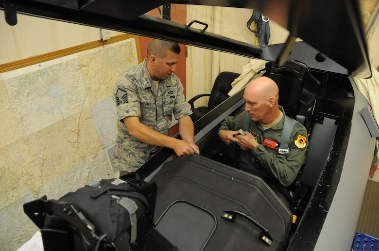 Master Sgt. Kenneth Shearer, 114th Fighter Squadron, instructs Maj. Gen. Timothy Zadalis, Director of Intelligence Operations and Nuclear Integration Headquarters at Air Education and Training Command, on F-15 egress in preparation for Zadalis' familiarization flight in an F-15 Eagle at Kingsley Field, Ore., July 24, 2012. Kingsley Field was just moved under the command of Zadalis earlier this year. (Air National Guard photo by Tech. Sgt. Jefferson Thompson/Released)