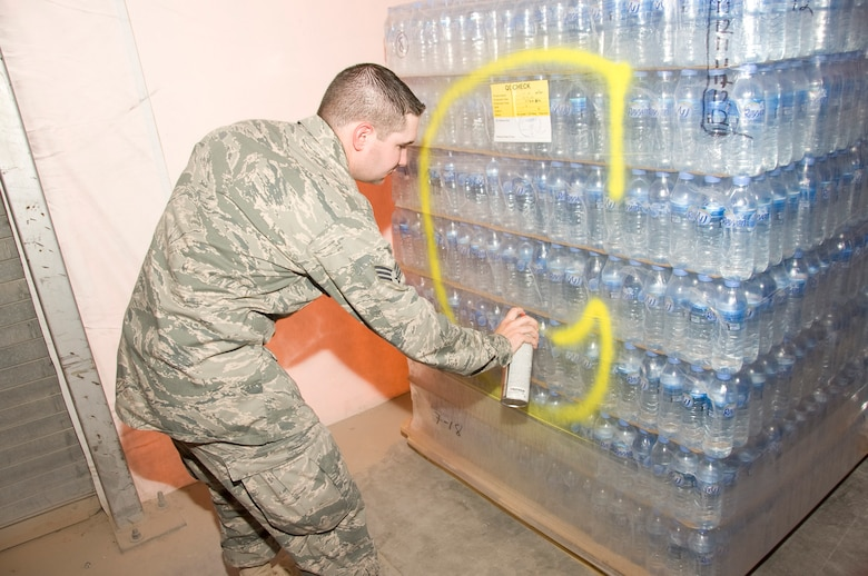 Senior Airman Ryan Smith, 379th Expeditionary Medical Group Bioenvironmental environmental program manager, spray paints a pallet of bottled water July 20, 2012. After each lot of water has been cleared and deemed safe for consumption, Smith marks the pallet of water with a large, yellow 'C'. He conducts bacteriological tests on every batch of water received. (U.S. Air Force photo/Senior Airman Bryan Swink)