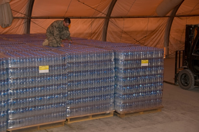 Senior Airman Ryan Smith, 379th Expeditionary Medical Group Bioenvironmental environmental program manager, pulls a random bottle of water from a pallet of water with a specific production date. Smith pulls and tests random bottles from every shipment of water to ensure all water is free of any form of bacteria. More than 1.3 million bottles of water are consumed at this installation every month. (U.S. Air Force photo/Senior Airman Bryan Swink)